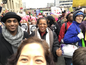 Marching in a crowd, selfie (eyes) with black man and woman behind me and sea of pink hats