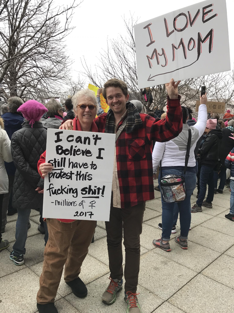 "Man and woman with signs: ""I can't believe I still have to protest this fucking shit – millions of women 2017"" and ""I love my mom"""