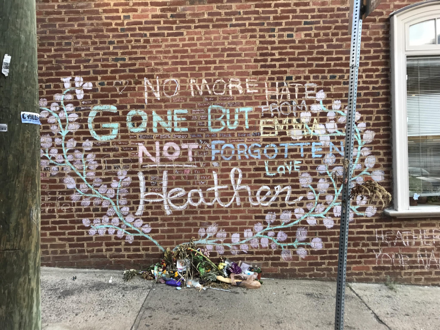 Brick wall with chalk drawings and flowers on the sidewalk, writing: No more hate, Gone but not forgotten Heather
